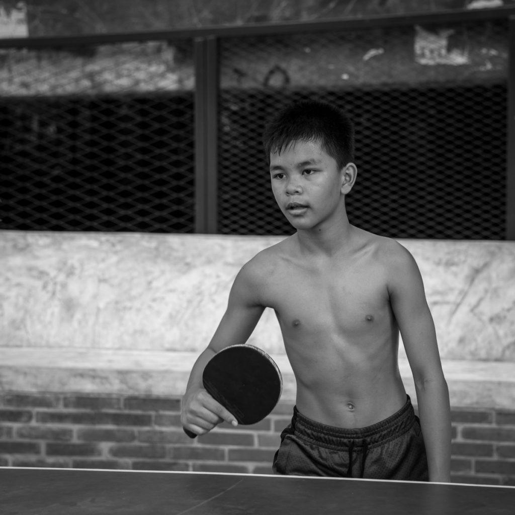 shirtless boy playing table tennis