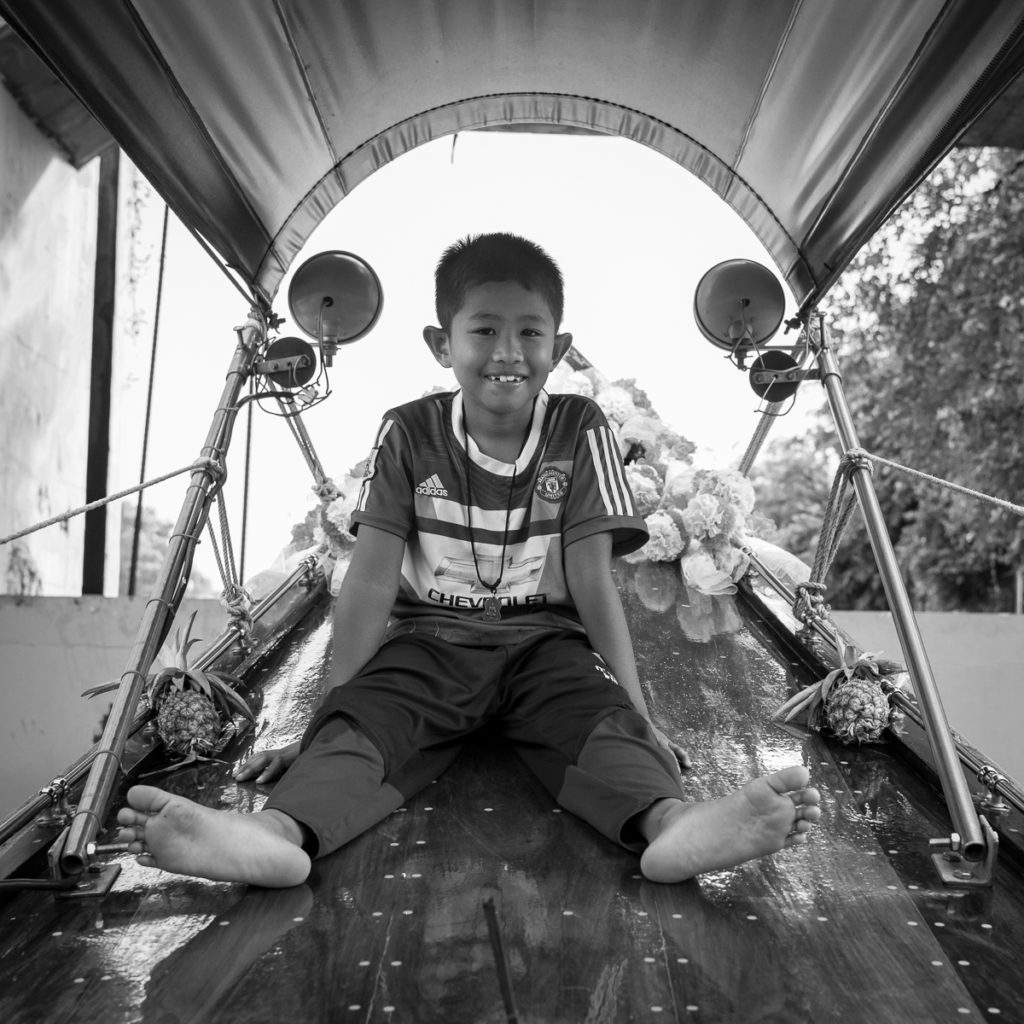 barefoot boy on a long-tail boat in Bangkok.