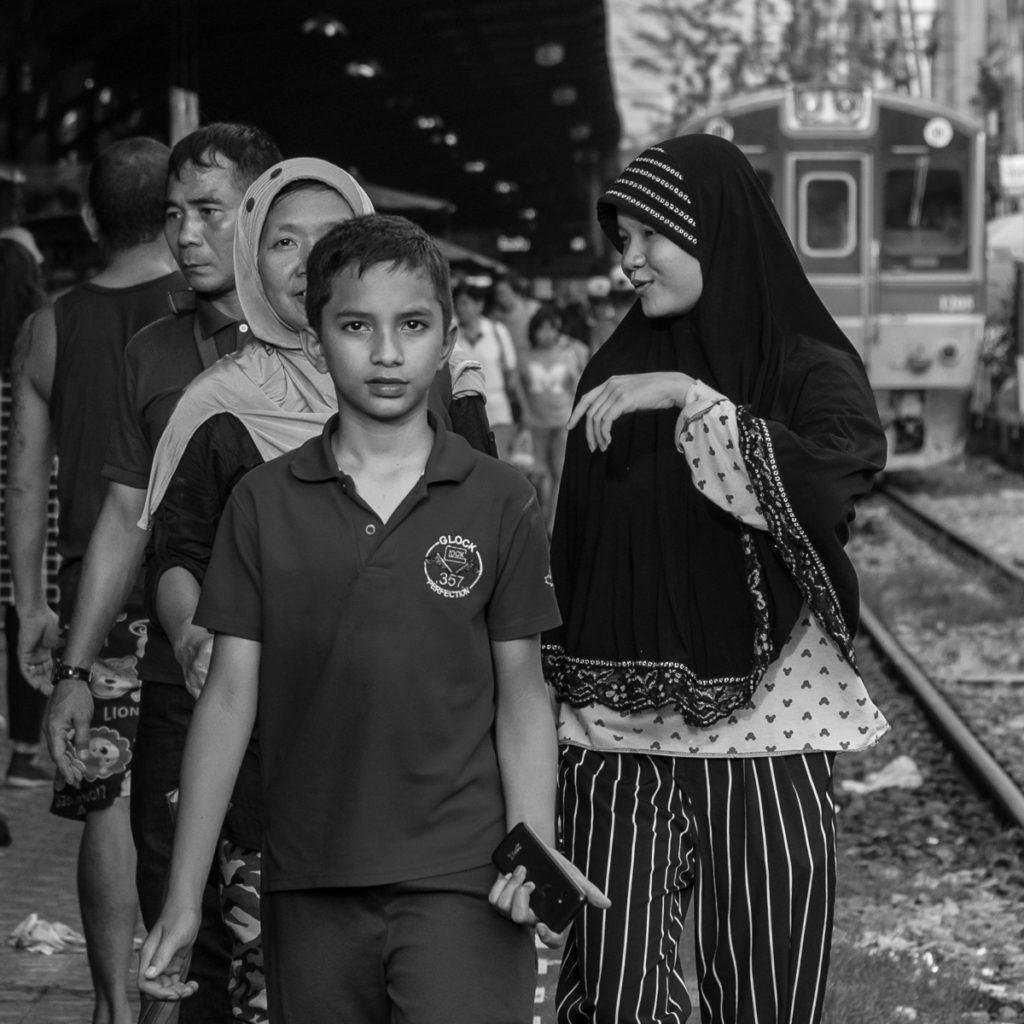 Muslim family in bangkok on railway train platform.