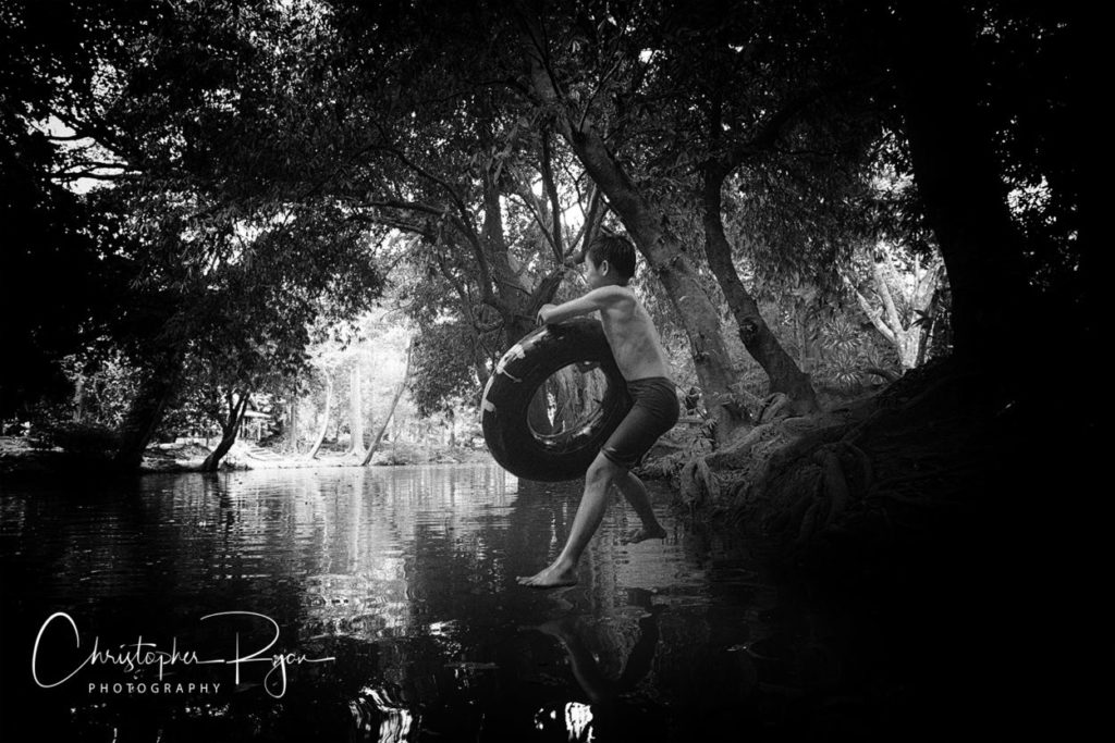 shirtless boy jumping into the river