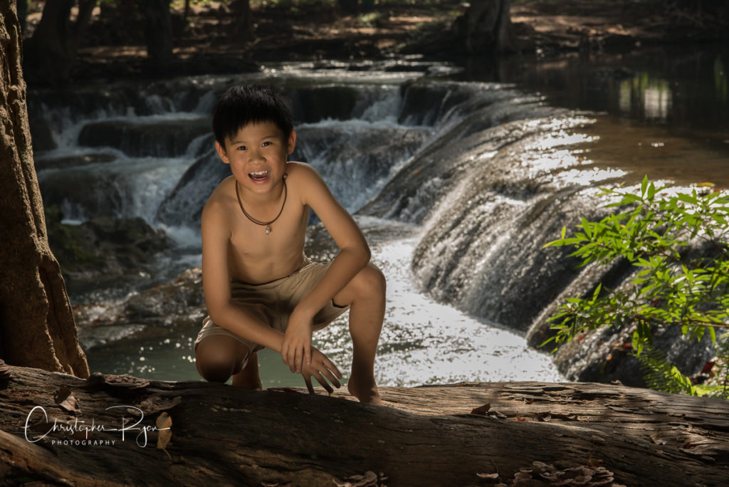 shirtless boy at waterfall