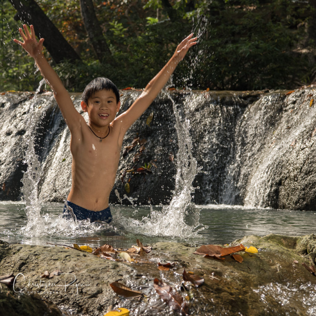 shirtless boy jumping out of water