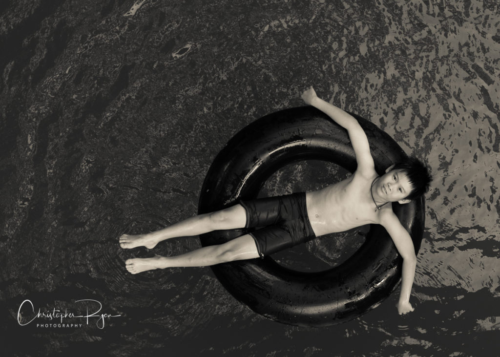 cute shirtless and barefoot boy floating on a tube in a river