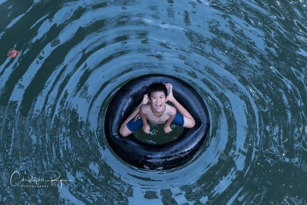 smiling shirtless barefoot boy on inner tube in the water