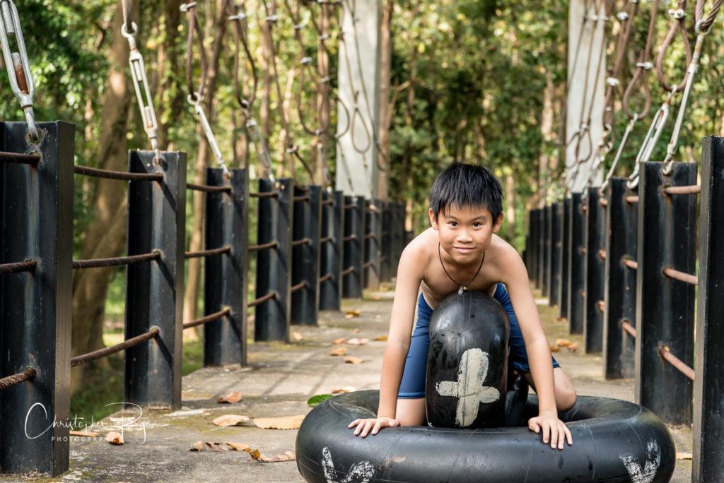 cute shirtless asian boy on a bridge