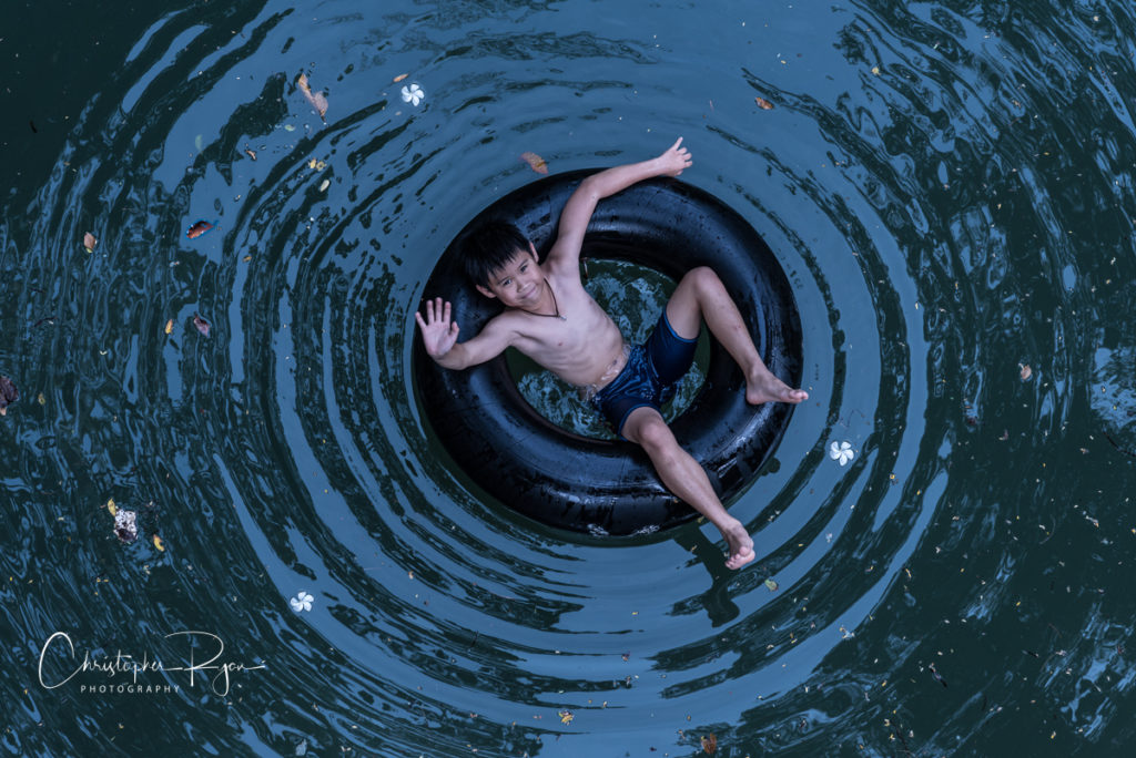 boy on inner tube in a river