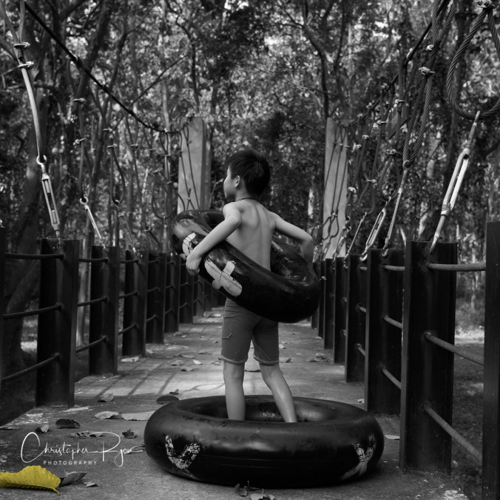 black and white (B&W) image of a shirtless boy on a swing bridge in nature