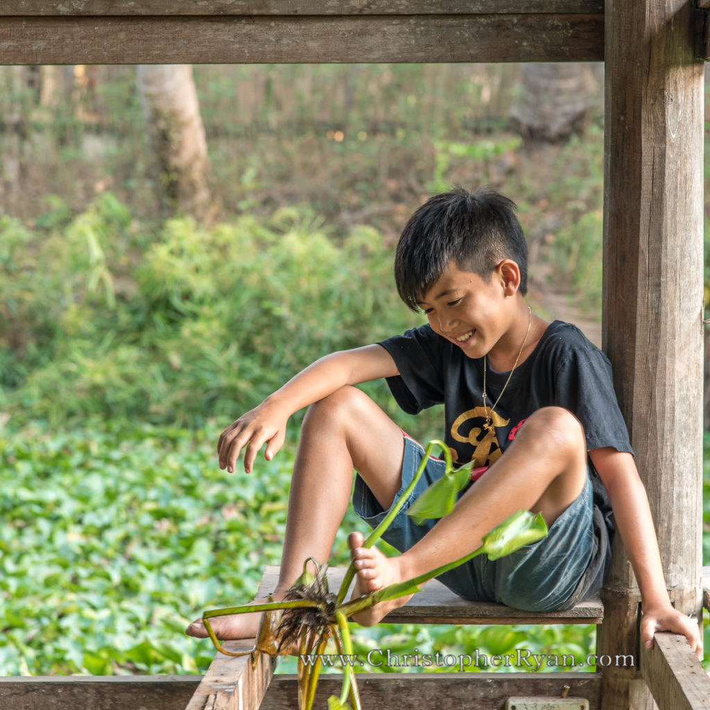 boy using feet to play with plant