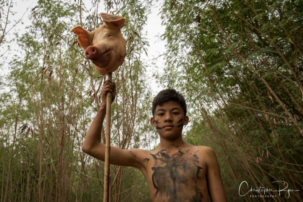 shirtless boy with pig's head