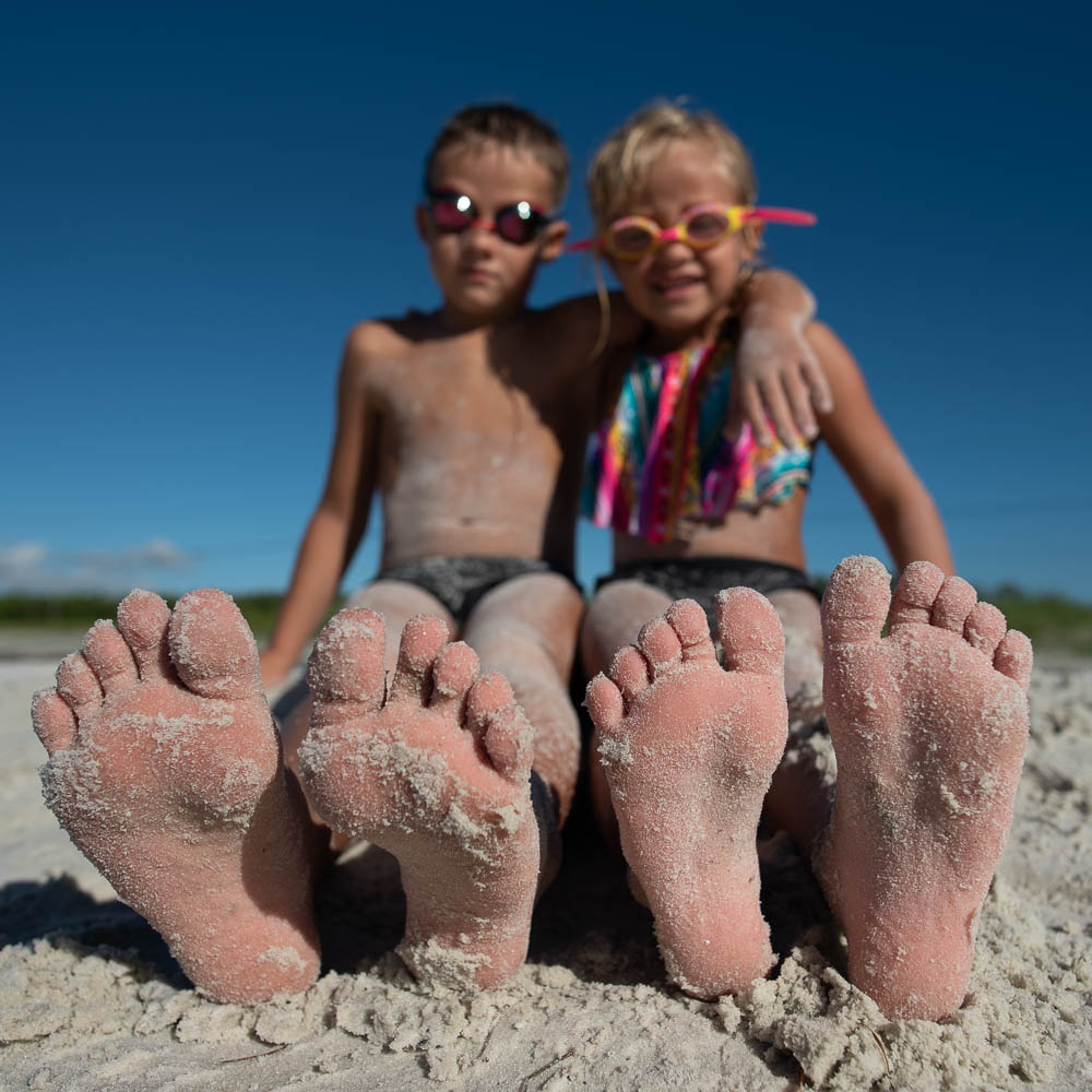 closeup shot of soles of a boy and girl's feet at the beach for focus on feet project