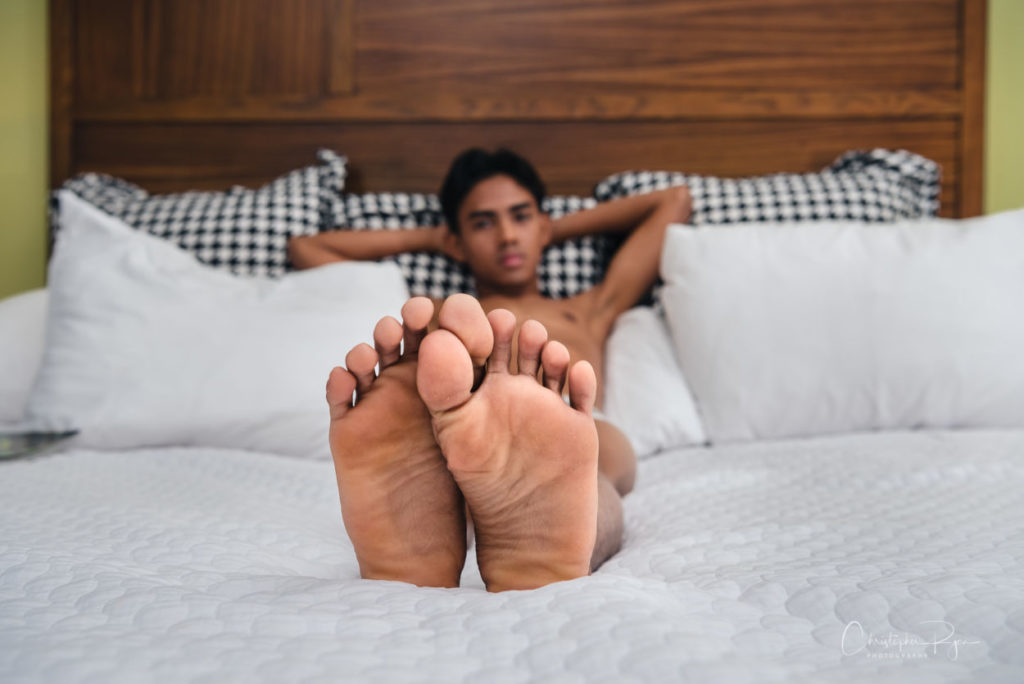 youthful asian male laying on a bed without shirt showing the soles of his feet