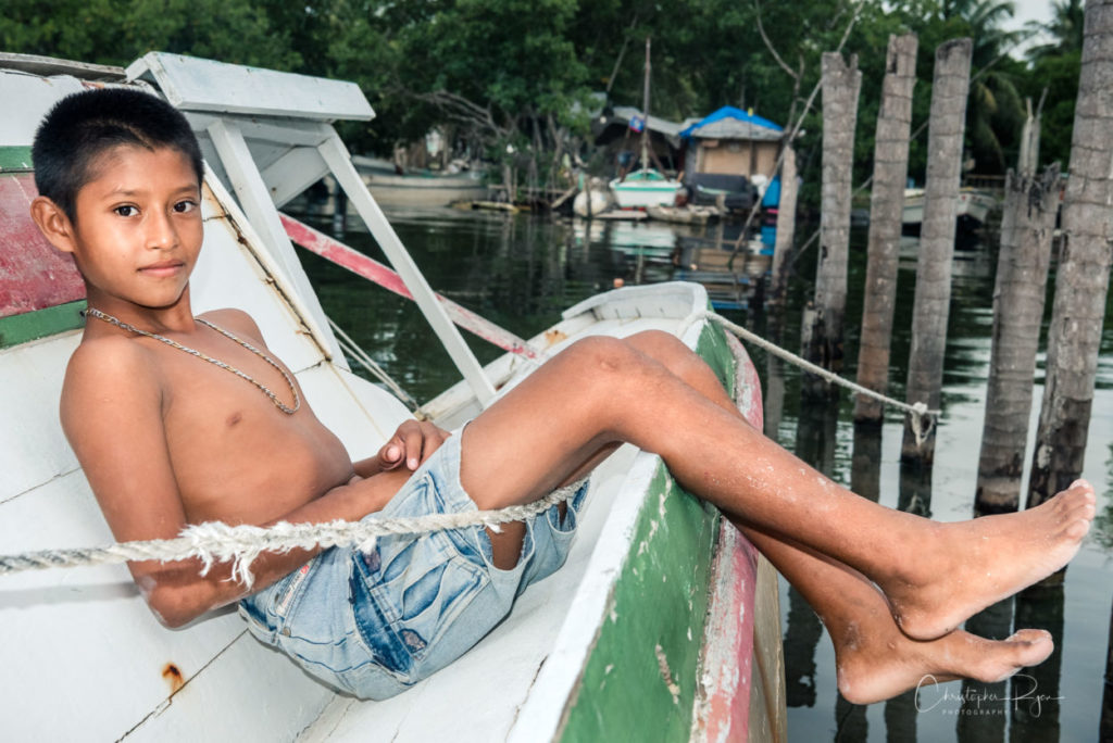 barefoot and shirtless boy relaxing on an abandoned sailboat in caye caulker belize