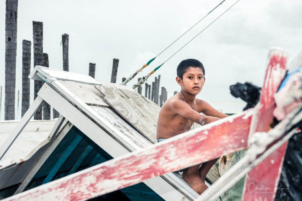 skinny shirtless boy sitting on a sinking boat in belize