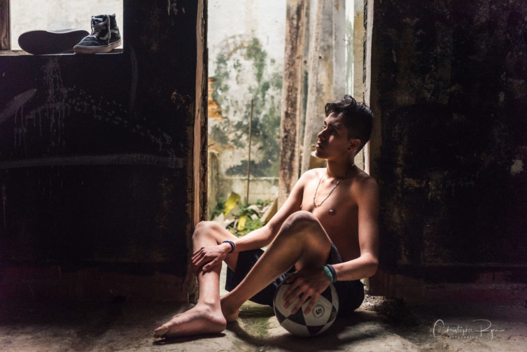 very beautiful barefoot and topless boy relaxing with soccer ball