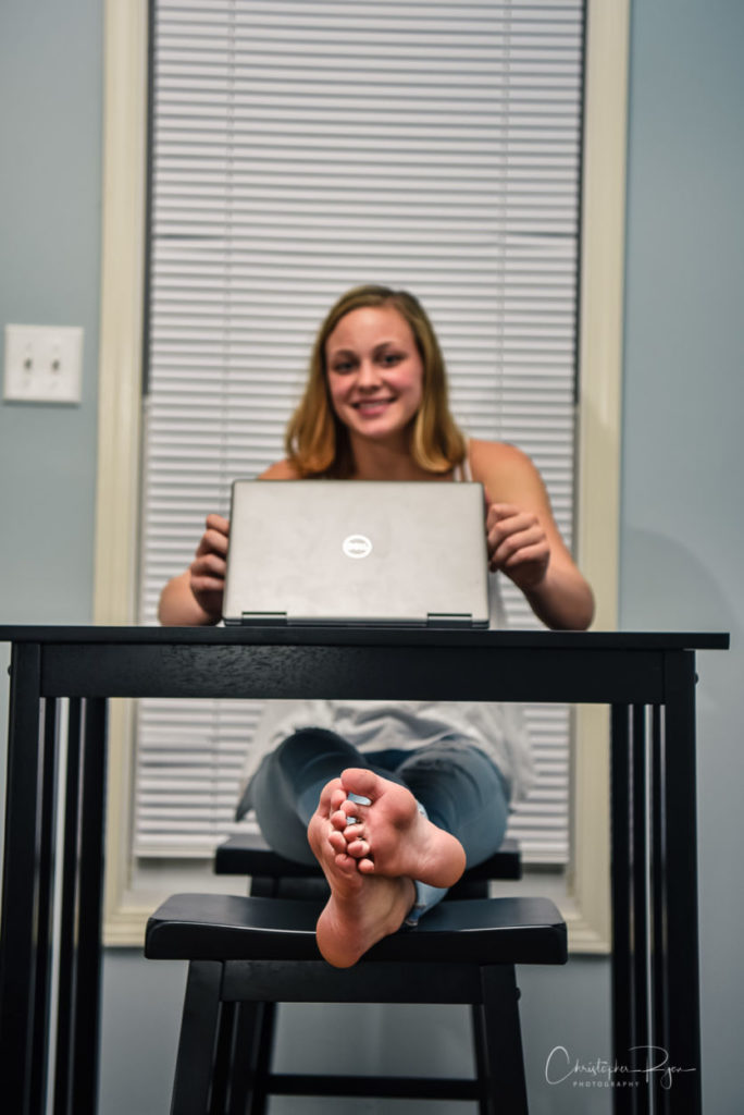 barefoot teen girl sitting at a desk with bare feet propped up on a chair