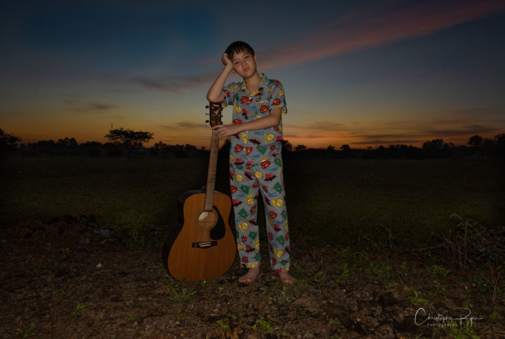 Korn from TV show Wekids Thailand is a 10 year old boy wearing pajamas holding a guitar.
