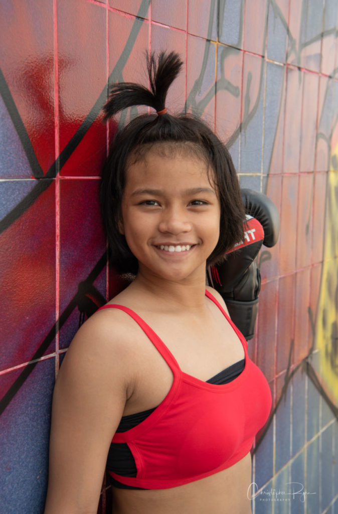 12 year old Muay Thai fighter girl in red sports bra in front of graffiti wall.