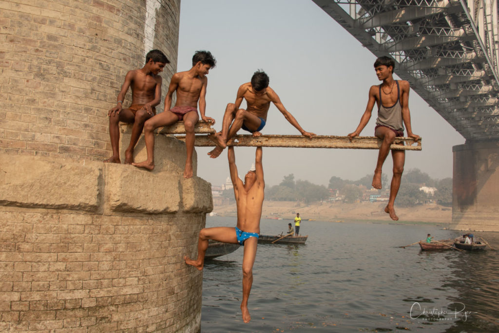 shirtless indian boys diving from train bridge