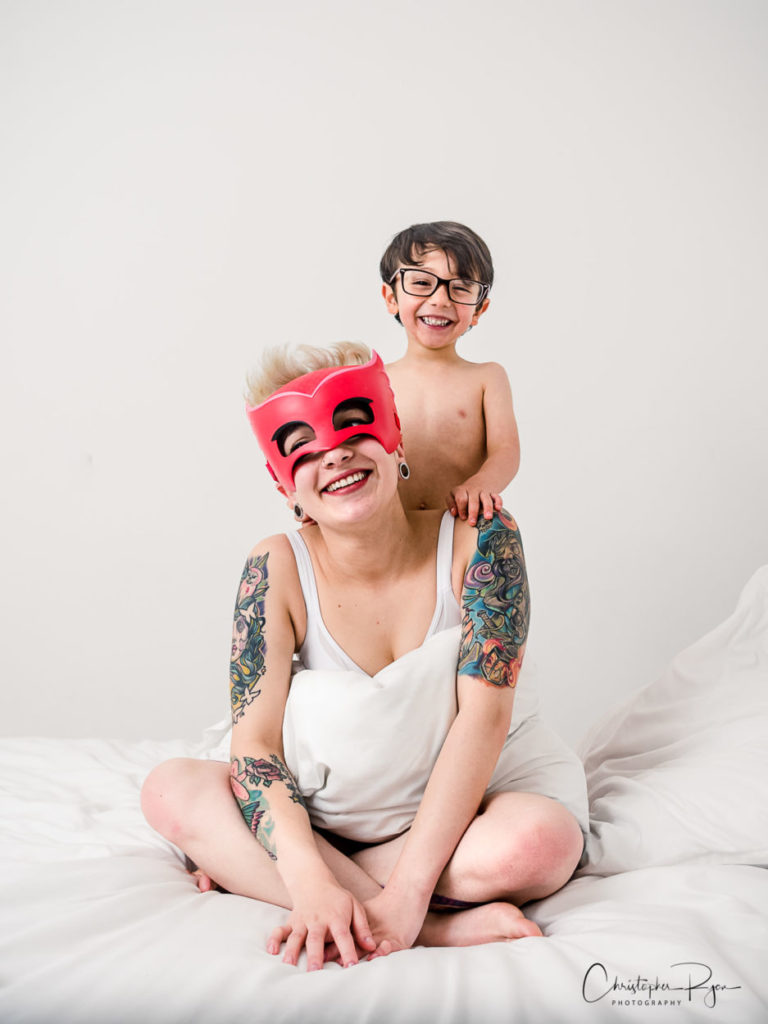 mom wearing mask in bed playing with young son
