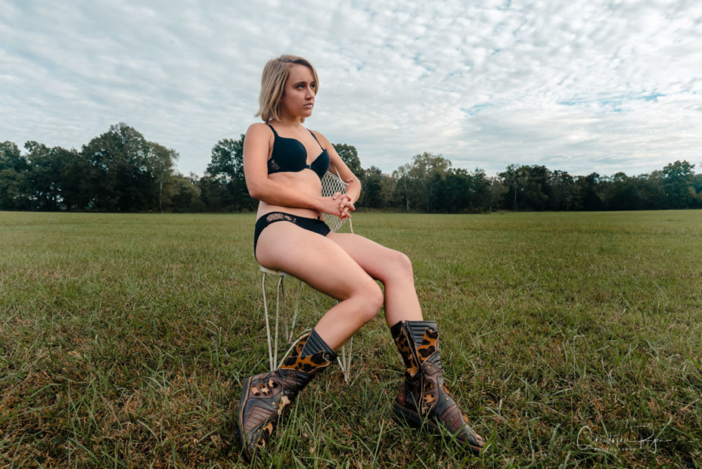 sexy girl in black panties, bra, and cowgirl boots
