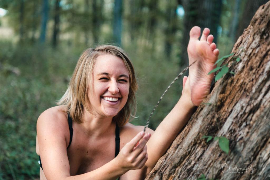 blond girl feather tickling her feet