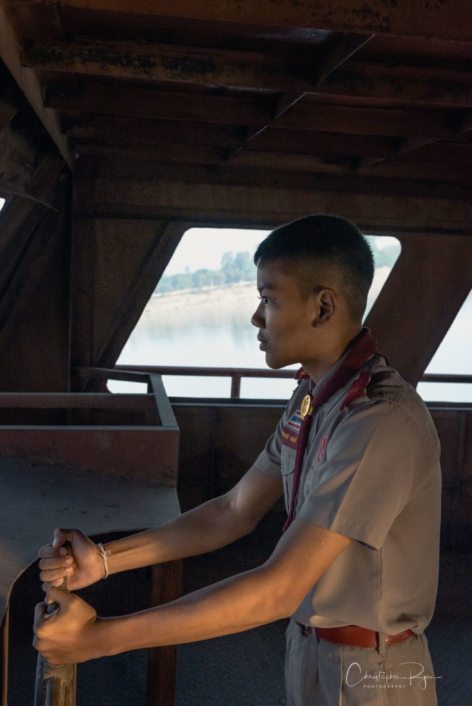 Thai boy scout at the helm of a river boat on the Mekong River.