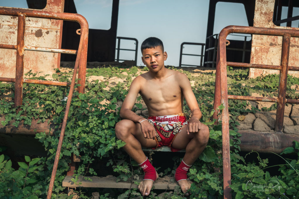 shirtless and barefoot boy in Muay Thai fighter on an abandoned boat.