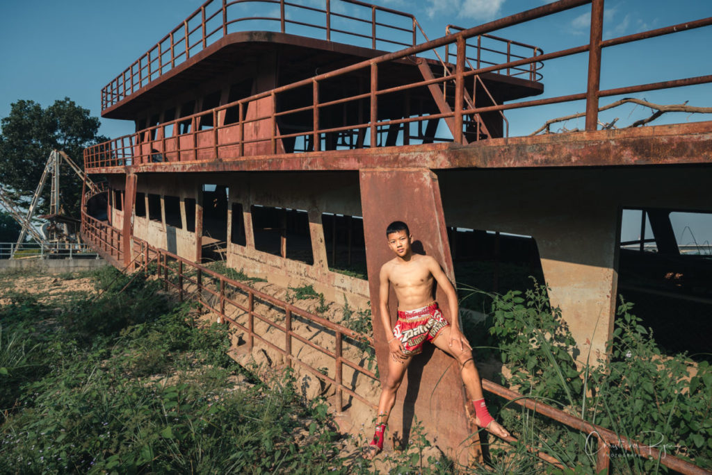 hull of rusty abandoned boat on the mekong river with cute shirtless teenage boy on the Mekong River.