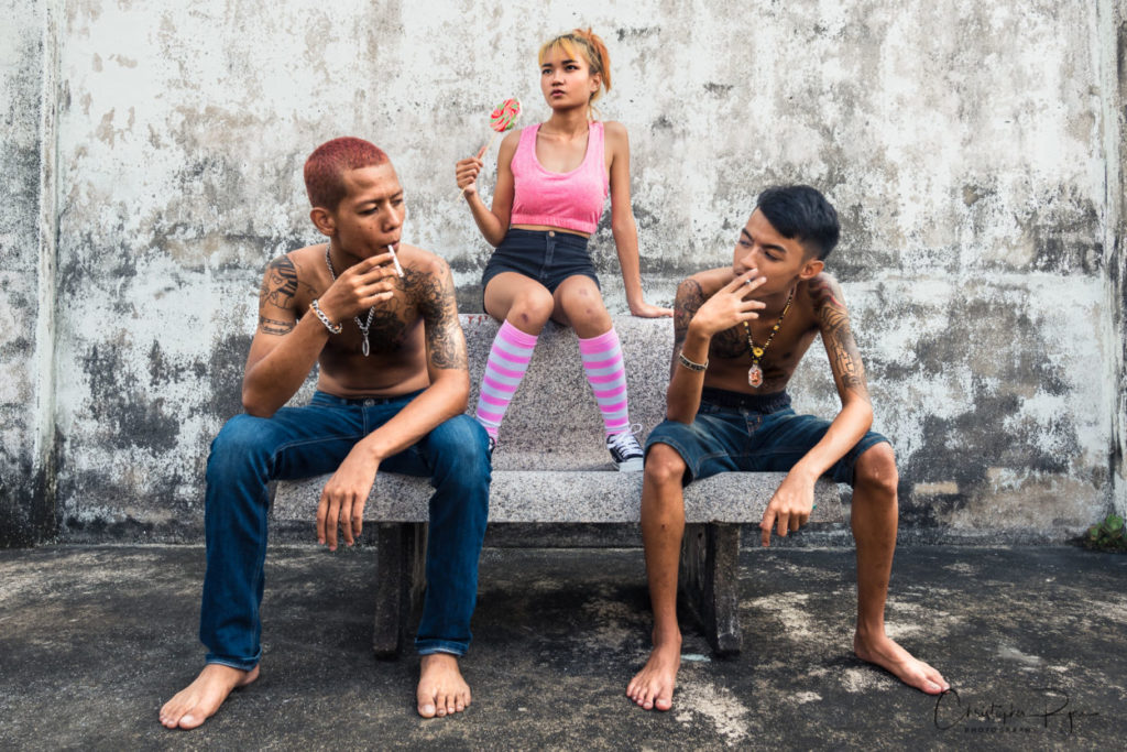 teenage girl with pink striped socks and pink sports bra with two shirtless tattooed boys