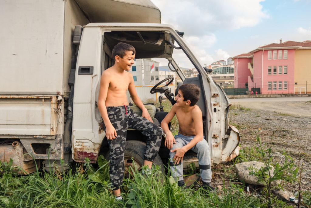 shirtless boys playing in a junkyard