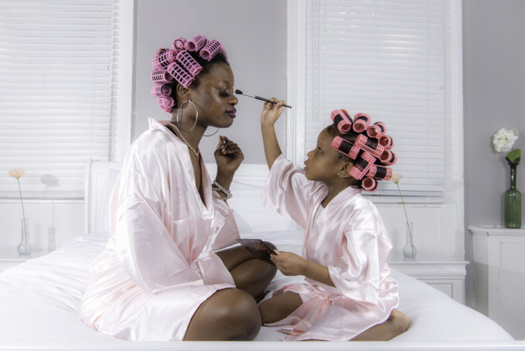 young girl applying makeup to her mother